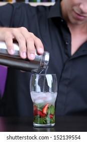 Portrait of handsome barman preparing cocktail, at bar