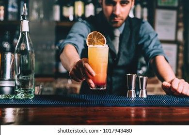Portrait of handsome bartender serving perfect summer drink, chilled rum with orange juice and tequilla