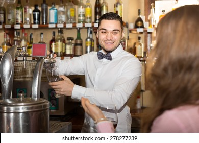 Portrait of handsome bartender working at counter of bar
