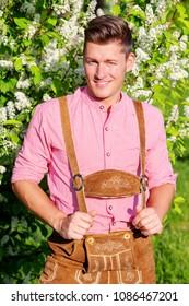 portrait of handsome bavarian blond man standing outdoors