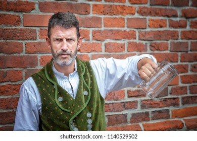 portrait of handsome bavarian man holding an empty beer mug
