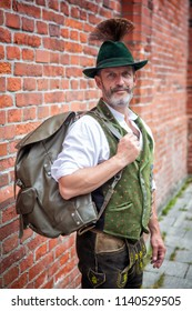 portrait of handsome bavarian man standing outside with backpack