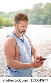 portrait of handsome bearded athlete outdoors looking at his phone