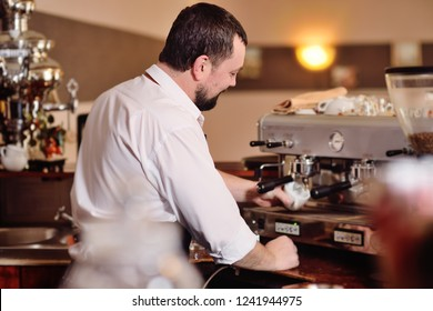 portrait of a handsome bearded barista preparing coffee on the background of a coffee shop and a coffee machine