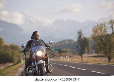 Portrait of handsome bearded biker in black leather jacket holding motorcycle handles on country roadside on blurred background of green landscape, distant white mountain peaks and bright sky.