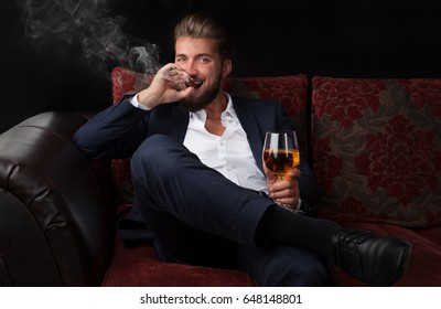 Portrait of a handsome bearded Businessman in elegant suit smoking a cigar and drinking a Whiskey