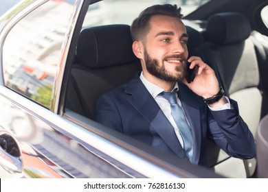 Portrait of handsome bearded businessman speaking by phone sitting in back seat of car and smiling happily