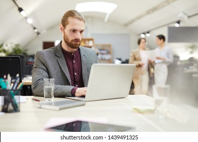Portrait of handsome bearded businessman using laptop while working in open space office