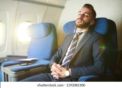 Portrait of handsome bearded businessman wearing earphones sleeping blissfully while enjoying first class flight in plane, copy space