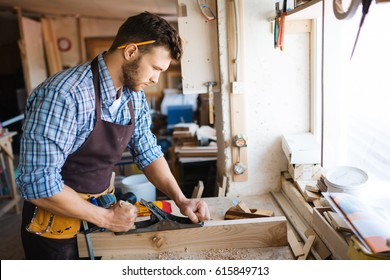 Portrait of handsome bearded carpenter with pencil behind his ear working with plank in workshop, profile view