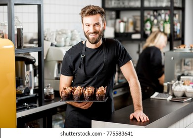 Portrait of a handsome bearded confectioner in black t-shirt and apron holding mafins at the cafe