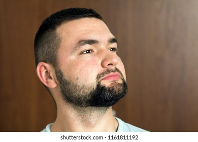 Portrait of handsome bearded confident intelligent modern photogenic young man with short haircut and black eyes looking thoughtfully ahead on blurred background. Youth and confidence concept.