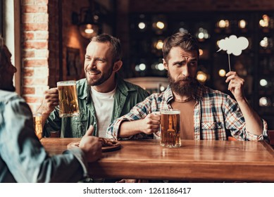 Portrait of handsome bearded gentleman chatting with friend while man in plaid shirt holding thought bubble and looking away with skeptical expression. Guys sitting at the table with beer and snacks