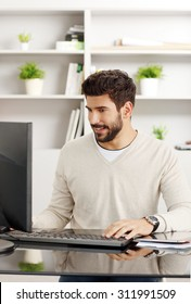 Portrait of handsome bearded graphic designer at workplace. Young creative man sitting in front of computer and checking emails. Small business.