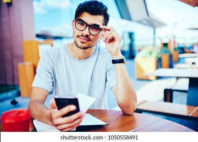 Portrait of handsome bearded hipster bloger in stylish eyeglasses looking at camera while updating profile in social networks on smartphone connected to free 4G internet connection sitting outdoors