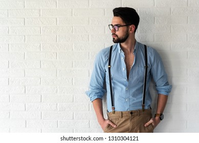 Portrait of handsome bearded hipster guy with glasses on standing indoors by the white brick wall