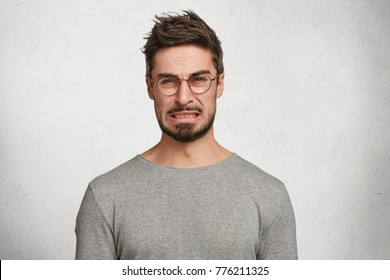 Portrait of handsome bearded male with disgusting expression sees sour lemon in front, frowns in displeasure, isolated over white concrete background. Male expresses aversion towards something