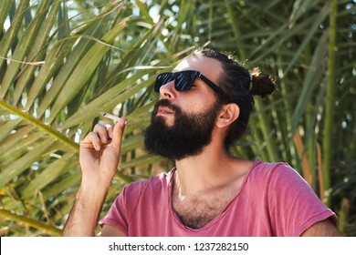 Portrait of a handsome bearded male hipster smoking a joint under a palm tree