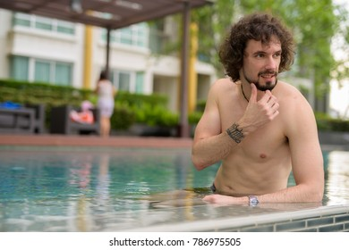Portrait of handsome bearded man with curly hair shirtless relaxing beside the swimming pool in the city of Bangkok, Thailand