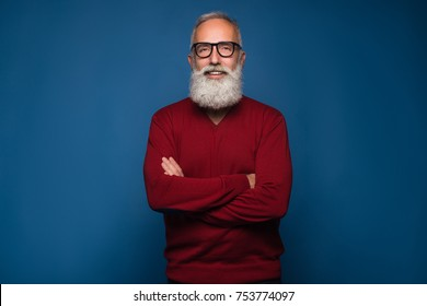 Portrait of handsome bearded man in fashion black glasses standing with arms folded isolated on a blue background in res sweeter. Happy bearded man look at the camera and smile
