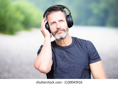 portrait of handsome bearded man with headphones outdoors