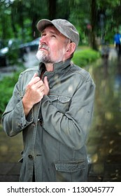 portrait of handsome bearded man in his 50s walking outdoors in the rain