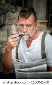 portrait of handsome bearded man in his 50s smoking a pipe and reading a newspaper