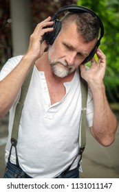 portrait of handsome bearded man in his 50s with headphones