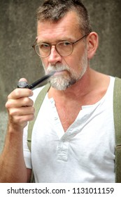 portrait of handsome bearded man in his 50s smoking a pipe