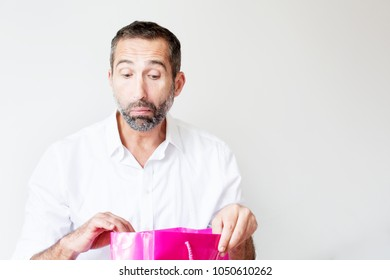 portrait of handsome bearded man looking in a giftbag