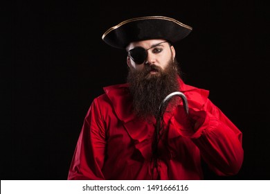 Portrait of handsome bearded man wearing medieval pirate clothes for halloween carnival. Man in pirate costume isolated over black background.
