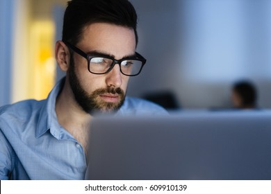 Portrait of handsome bearded man wearing glasses working with laptop in dark office late at night, his face lit up by screen