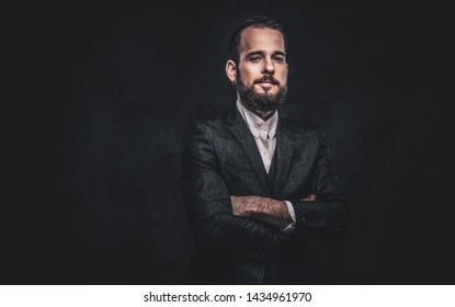 Portrait of handsome bearded stylish male, wearing an elegant suit on a dark background.