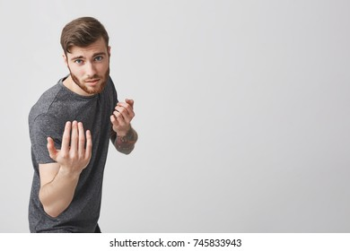 Portrait of handsome bearded tattooed caucasian man with stylish haircut in casual gray t-shirt looking in camera with mean and serious expression, making fun fight poses for photosession.
