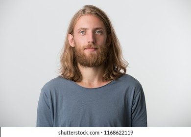Portrait of handsome bearded young man with blonde long hair wears gray t shirt looks serious and confident isolated over white background