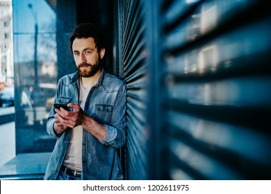 Portrait of handsome bearded young man dressed in denim wear looking at camera while holding digital smartphone and checking email on device using 4G internet standing outdoors near wall