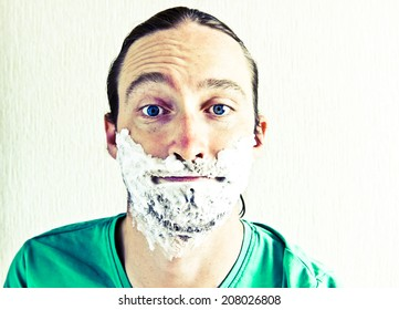 Portrait of handsome bearded young man with shaving foam on funny face. Image with vintage filter