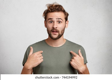 Portrait of handsome bearded young man points at himself being puzzled to be chosen. Astonished attractive European male stands over white background, has confused expression. Surprisment concept