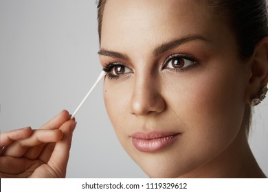 Portrait Handsome beauty girl refreshing skin face with white cotton buds over gray studio background.Model with light nude make-up.Healthcare skin makeup concept