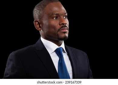 Portrait of an handsome black businessman. Dark background