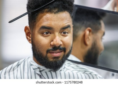 Portrait of handsome black man with comb in curly hair looking in the mirror at his new haircut.Barber hairdresser showing client his work.Male beauty treatment concept.Pretty young African guy face