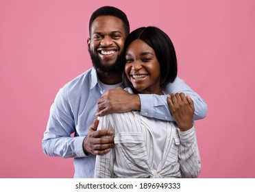Portrait of handsome black man and his beautiful girlfriend hugging and looking at camera on pink studio background. Loving African American couple posing and smiling. Valentine's Day concept