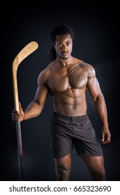 Portrait of a handsome black man posing shirtless for camera with hockey stick in his hands