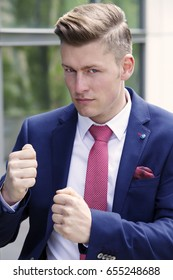 portrait of handsome blond businessman posing as a boxer