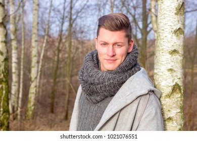 portrait of handsome blond man in forest in the cold