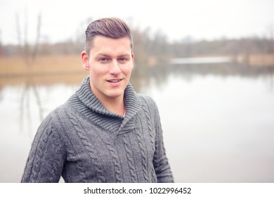 portrait of handsome blond man in front of lake