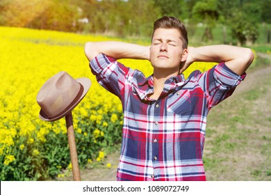 portrait of handsome blond man in front of yellow field enjoying the sun