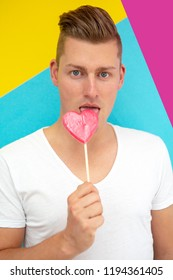 portrait of handsome blond man licking on heart shaped lollipop