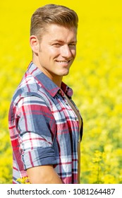 portrait of handsome blond man with open shirt standing in a yellow field