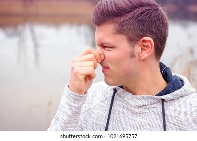 portrait of handsome blond man smelling something bad
